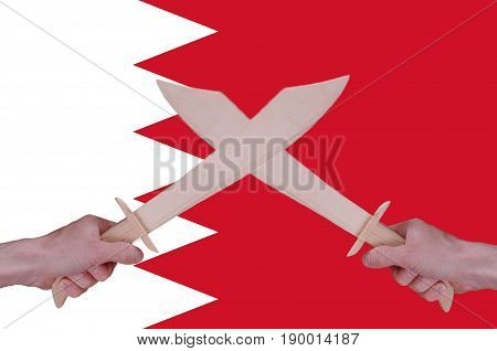 Hands hold crossed wooden sabres, Bahrain flag visible on the background.