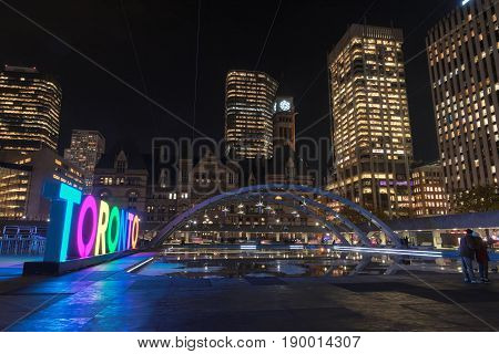 Toronto sign and Old City Hall in Nathan Phillips Square at night