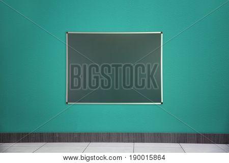 Blank blackboard on color wall in empty class room