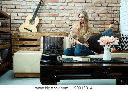 Young woman resting at home on sofa, using mobilephone.