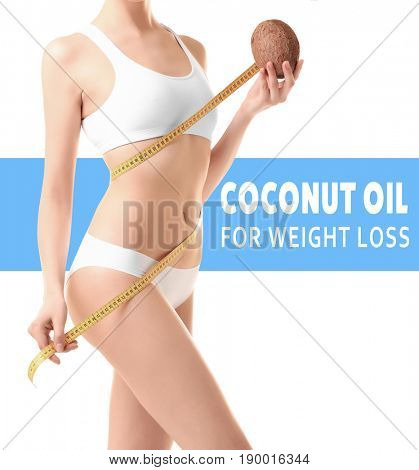 Young woman holding nut and measure tape on white background. Coconut oil for weight loss