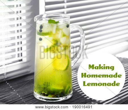 Glass jug of refreshing drink with lime and blueberry on wooden windowsill. Text MAKING HOMEMADE LEMONADE on background