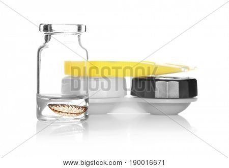 Glass bottle with brown lens, container and tweezers on white background