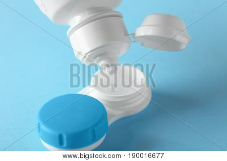 Bottle of solution and container for contact lenses on color background