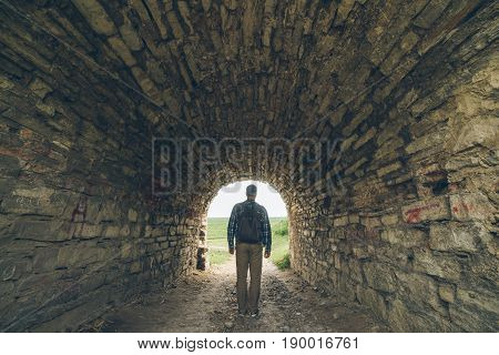 man stands in old castle tunnel with light in the end