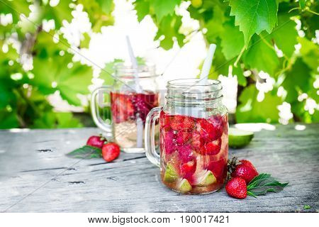 Strawberry lemonade with lime in mason jar on a wooden table Against the background of grapevines