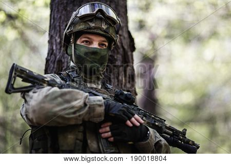 Portrait of officer with submachine gun standing in woods during day