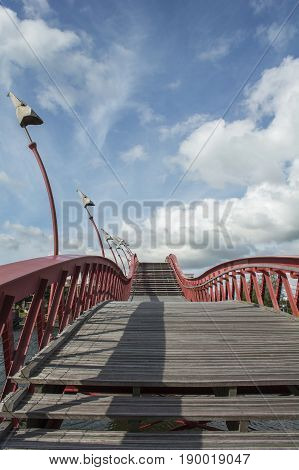 Wooden stairway with red banister in the blue sky with clouds in the daylight