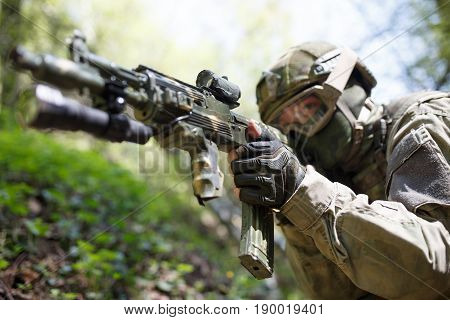 Portrait of officer with submachine gun on military mission in forest