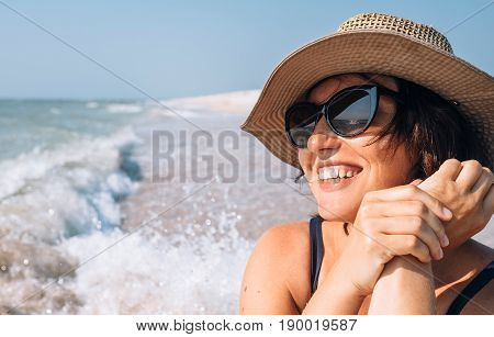 Happy smiling woman in straw hat on the sea beach