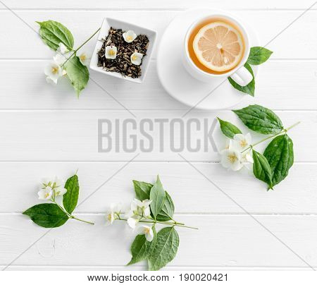 Teatime with jasmine green steaming tea, piece of lemon, jasmine flowers, space for text, topview