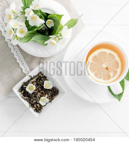 White ceramic cup full of green jasmine tea with slice of lemon, jasmine petals, topview