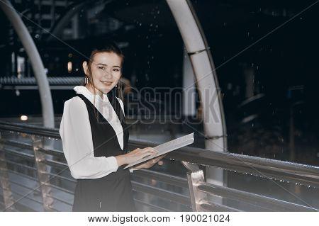 Asian Pretty woman in black dress writing document on rainy day stands on crossing bridge landmark of Bangkok city.