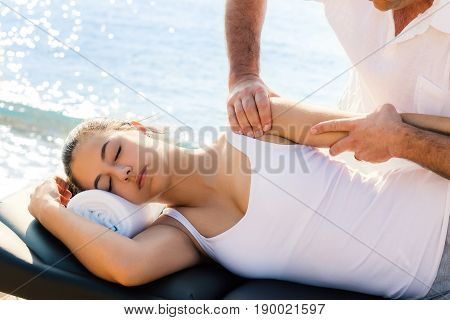 Close up of male osteopath doing shoulder and arm therapy on young female athlete on location next to sea.