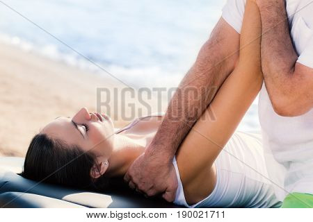 Close up of male osteopath doing arm and shoulder treatment on young female athlete outdoors next to sea side.