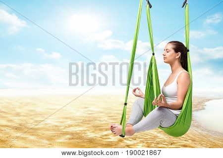 Conceptual portrait of young woman sitting in antigravity yoga hammock with eyes closed.Girl doing spiritual exercise against river bed and blue sky.