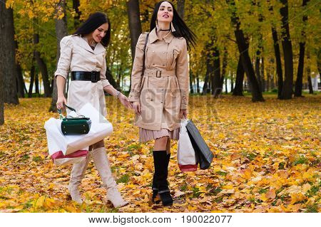 two girlfriends walking park with shopping in hands