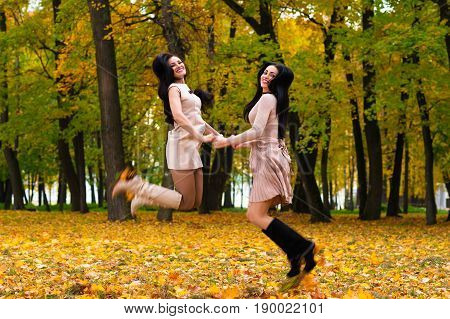 two beautiful brunette girls jumping on background autumn park