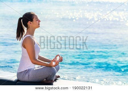 Full length portrait of young woman meditating next to sea. Side view of girl doing yoga exercise in early morning sun with bright reflection on water surface.