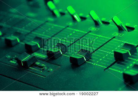 Sound mixer console under green disco light