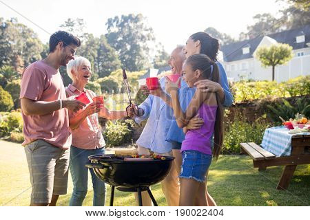 Happy family laughing and talking while preparing barbecue in the park