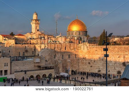 Sunset view of Temple Mount in the old city of Jerusalem, including the Western Wall and golden Dome of the Rock, packed with people - pilgrims and tourists.