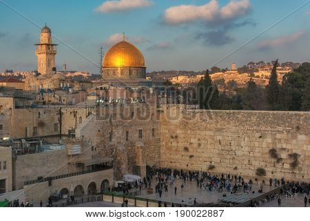 Western Wall and golden Dome of the Rock at sunset.