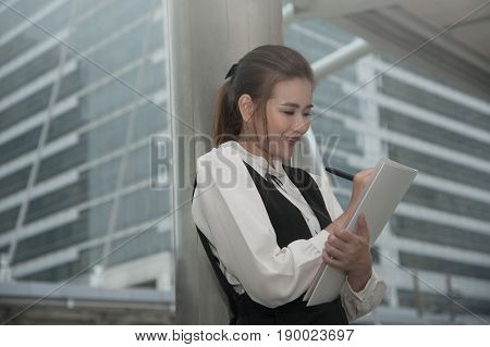 Asian Pretty woman in black dress writing document stand on crossing bridge landmark of Bangkok city.