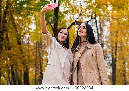 charming women do selfie on autumn background