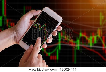 Business woman hand touch screen on smart phonetabletcellphone with blured stock chart background. with filtered red color abstract background to forex and stock concept.