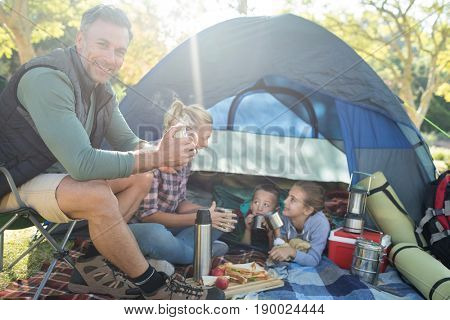 Smiling family having snacks and coffee outside the tent at campsite