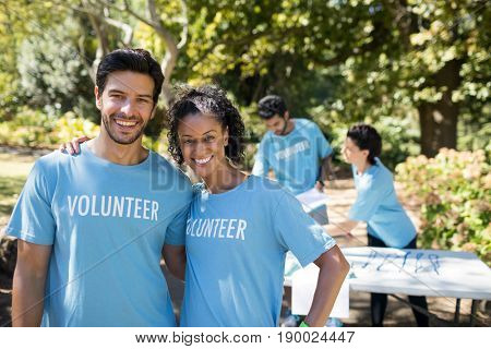 Portrait of smiling volunteers standing in the park