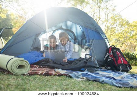 Kids using laptop in the tent at campsite