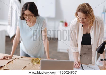 Concentrated on work. Pretty brunette tailor looking at dress patterns while her blonde colleague checking the notes when developing a new outfit.