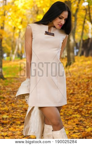 beautiful brunette in fashion dress on background of autumn park