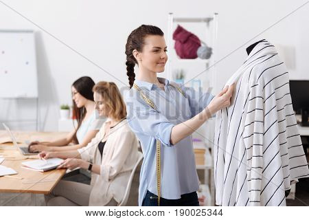 Nicely done. Pretty young woman holding lapels of a cardigan hanging on a mannequin while her colleagues developing outfit sketches