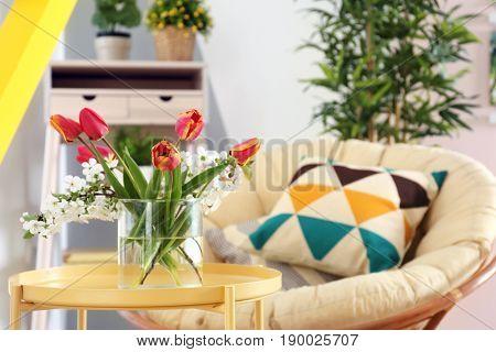 Vase with beautiful flowers in modern veranda interior