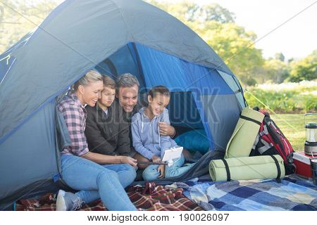 Family taking a selfie in the tent at campsite