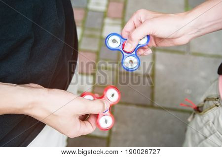 Close-up Two boyfriends tweens spinners on the street against each other Two fidget spinners