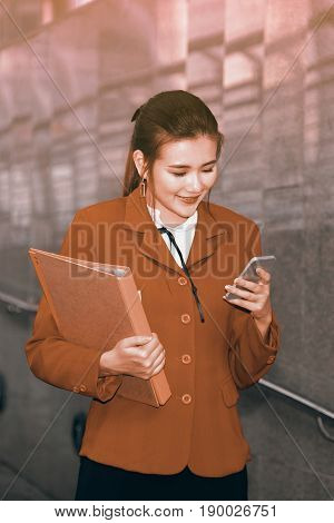Asian Pretty woman in red suit holding document and use smart phone standing on crossing bridge landmark of Bangkok city.