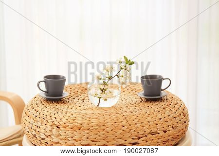 Two cups and vase with beautiful flowers on rattan table at home