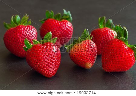Fresh strawberries on granite background. Ripe strawberry stack on granite table.