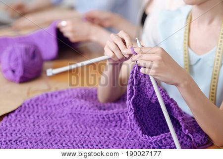 Fine workmanship. The focus being on dainty female hands knitting a scarf with purple threads in a chunky knit manner.