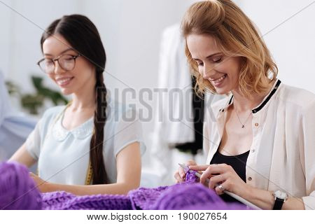 Pleasure of creation. Two gorgeous pleasant women knitting with purple threads and seemingly enjoying themselves during this pastime