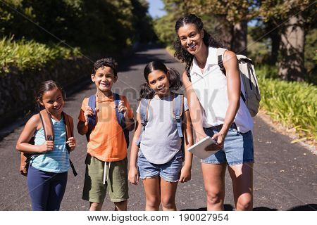 Portrait of happy teacher and students with tablet PC on street during summer field trip