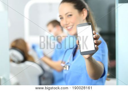 Stomatologist showing phone screen and looking at you in a dentist office interior with a doctor working in the background