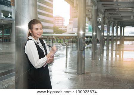 Asian Pretty woman in black dress writing document stand in rainy day on crossing bridge landmark of Bangkok.