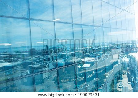 Full frame shot of office building exterior with reflection of city against sky