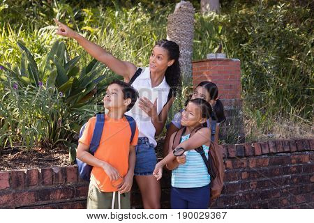 Teacher pointing to children at nature reserve during field trip