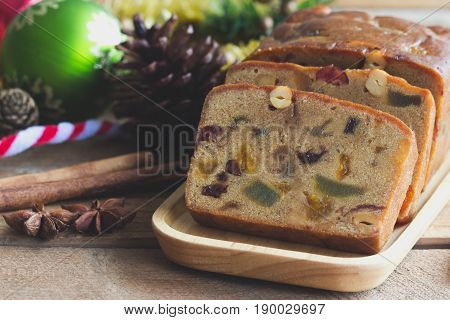 Homemade fruit cake on wood plate. Rum fruit cake with dried fruits made for Christmas celebration. Traditional homemade fruit cake so delicious rich and moist.